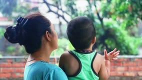 Moeder en dochter die van de regen genieten stock footage