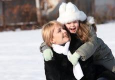 Moeder en dochter die van mooie de winterdag genieten Stock Foto's