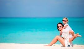 Moeder en dochter die van tijd genieten samen bij tropisch strand stock foto