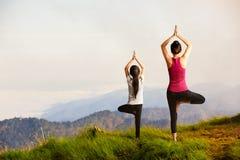 Moeder en dochter die yoga doen stock afbeeldingen