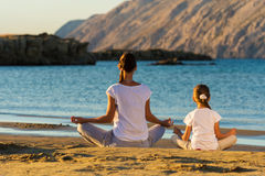 Moeder en dochter die yogaoefening op het strand doen Stock Foto