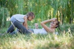 Moeder en dochter die yogaoefeningen op gras in het park doen in de dagtijd Royalty-vrije Stock Foto's