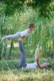 Moeder en dochter die yogaoefeningen op gras in het park doen in de dagtijd Stock Afbeeldingen