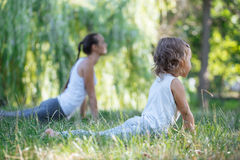 Moeder en dochter die yogaoefeningen op gras in het park doen in de dagtijd Royalty-vrije Stock Foto