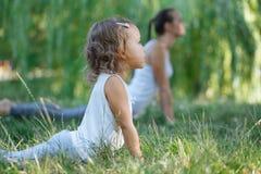 Moeder en dochter die yogaoefeningen op gras in het park doen in de dagtijd Royalty-vrije Stock Afbeeldingen