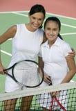 Moeder en dochter die zich bij netto op hoge de hoekmening van het tennisbaanportret bevinden stock fotografie