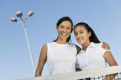 Moeder en dochter die zich bij netto op lage de hoekmening van het tennisbaanportret bevinden Stock Afbeeldingen