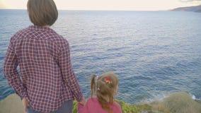 Moeder en dochter die zich bovenop een berg bevinden en het overzees bekijken Zonsondergang stock footage