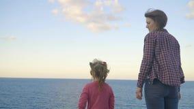 Moeder en dochter die zich bovenop een berg bevinden en het overzees bekijken Zonsondergang Griekenland kreta stock videobeelden