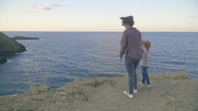 Moeder en dochter die zich bovenop een klip op een eiland bevinden die de oceaan bekijken Zonsondergang Griekenland kreta stock footage