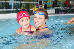 Moeder en dochter die in zwembad genieten van stock fotografie