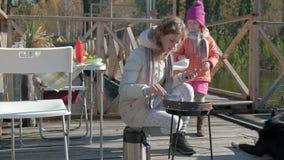 Moeder en dochter, een jonge vrouw en een klein meisje die in warme kleren, groenten en vlees op de grill voorbereiden, het gebru stock videobeelden