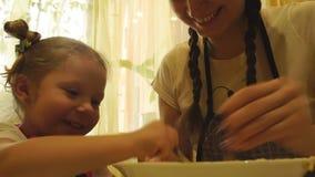 Moeder en dochter het kneden deeg Het kader van de bodem stock videobeelden