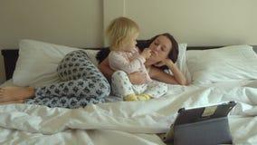 Moeder en dochter het letten op beeldverhalen op tabletcomputer stock video