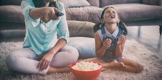 Moeder en dochter het letten op televisie terwijl het hebben van popcorn in woonkamer royalty-vrije stock foto's