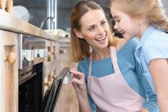 Moeder en dochter het openen oven terwijl het bakken van koekjes royalty-vrije stock afbeeldingen