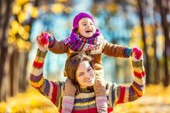 Moeder en dochter het spelen in de herfstpark Royalty-vrije Stock Afbeelding