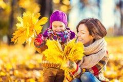 Moeder en dochter het spelen in de herfstpark Royalty-vrije Stock Afbeeldingen