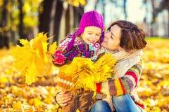 Moeder en dochter het spelen in de herfstpark Stock Afbeelding
