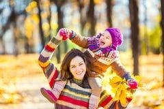 Moeder en dochter het spelen in de herfstpark Stock Foto