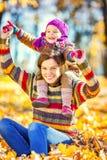 Moeder en dochter het spelen in de herfstpark Stock Afbeeldingen