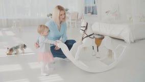 Moeder en dochter het spelen dichtbij schommeling Langzame Motie Gelukkige van de blondevrouw en baby zitting dichtbij schommelin stock videobeelden