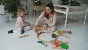 Moeder en dochter het spelen met spoorwegstuk speelgoed stock videobeelden