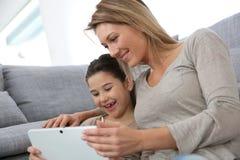 Moeder en dochter het spelen met tablet stock foto
