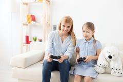 Moeder en dochter het spelen op console stock fotografie