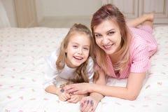 Moeder en dochter het spelen op een bed samen stock afbeelding