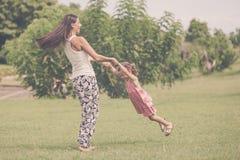 Moeder en dochter het spelen op het gras in de dagtijd Stock Foto