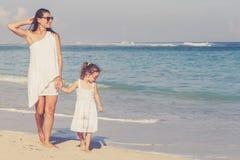 Moeder en dochter het spelen op het strand in de dagtijd Royalty-vrije Stock Afbeeldingen