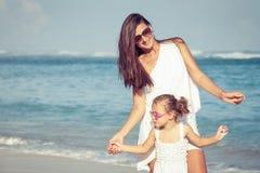 Moeder en dochter het spelen op het strand in de dagtijd Stock Fotografie