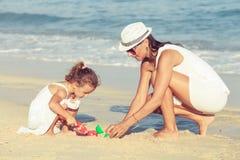 Moeder en dochter het spelen op het strand in de dagtijd Stock Afbeelding