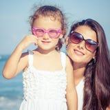 Moeder en dochter het spelen op het strand in de dagtijd Stock Foto's
