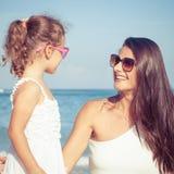 Moeder en dochter het spelen op het strand in de dagtijd Stock Afbeeldingen