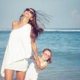 Moeder en dochter het spelen op het strand in de dagtijd Stock Foto