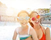Moeder en dochter het spelen in zwembad stock afbeelding