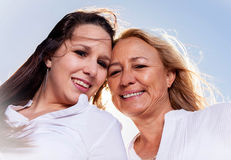 Moeder en dochter het stellen in de de zomerzon Stock Foto's