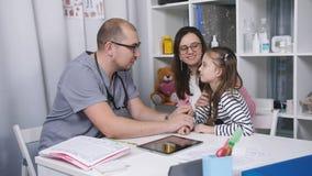 Moeder en dochter in het ziekenhuis voor de arts Vriendschappelijke arts die aan Moeder en kindpatiënt in bureau spreken stock video