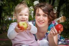 Moeder en dochter met appel in de hand stock foto's