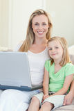 Moeder en dochter met laptop op bank Stock Afbeeldingen