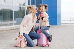 Moeder en dochter met roze bagage in roze jasje tegen de luchthaven Stock Foto