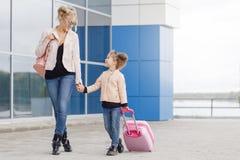 Moeder en dochter met roze bagage in roze jasje tegen de luchthaven Stock Afbeeldingen