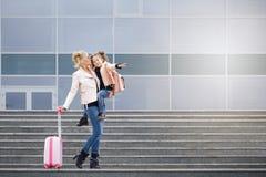Moeder en dochter met roze bagage in roze jasje tegen de luchthaven Royalty-vrije Stock Afbeeldingen