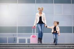 Moeder en dochter met roze bagage in roze jasje tegen de luchthaven Royalty-vrije Stock Fotografie