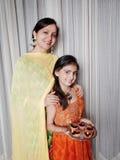 Moeder en dochter met verlichte Diyas op Diwali Stock Foto's