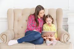 Moeder en dochter op bank thuis en samen spelend met PC-tablet stock afbeelding