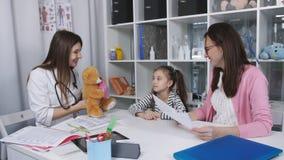 Moeder en dochter op de arts bij de medische kliniek Het vrouwelijke arts spreken met moeder en kind, geeft een weinig stock videobeelden