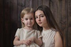 Moeder en dochter op donkere houten achtergrond royalty-vrije stock afbeeldingen
